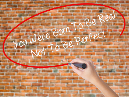true born: Woman Hand Writing You Were Born To Be Real Not To Be Perfect with black marker on visual screen. Isolated on bricks. Business, technology, internet concept.