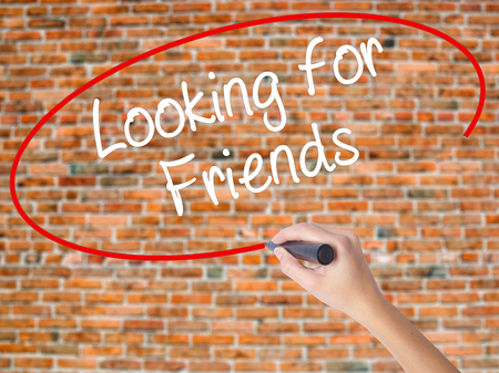 help me: Woman Hand Writing Looking for Friends with black marker on visual screen. Isolated on bricks. Business concept. Stock Photo