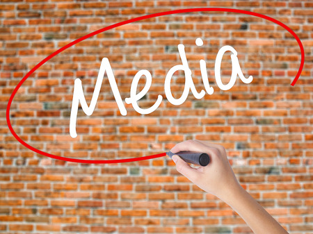 Woman Hand Writing Media with black marker on visual screen. Isolated on bricks. Business concept. Stock Photo Stock Photo