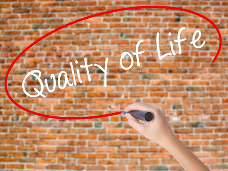 Woman Hand Writing Quality of Life with black marker on visual screen. Isolated on bricks. Business concept. Stock Photo
