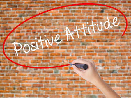 Woman Hand Writing Positive Attitude with black marker on visual screen. Isolated on bricks. Business concept. Stock Photo
