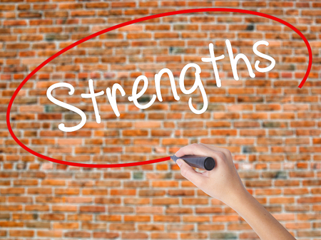 Woman Hand Writing Strengths with black marker on visual screen. Isolated on bricks. Business concept. Stock Photo