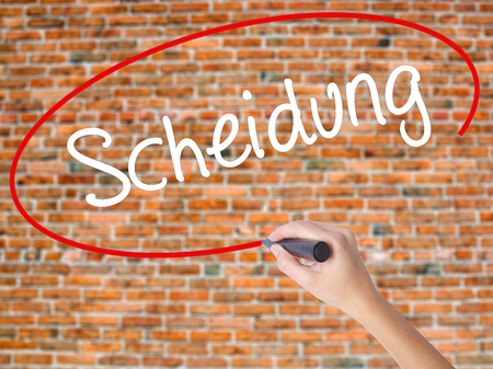 Woman Hand Writing Scheidung (Divorce in German) with black marker on visual screen. Isolated on bricks. Business concept. Stock Photo Stock Photo
