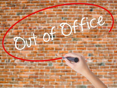 Woman Hand Writing Out of Office with black marker on visual screen. Isolated on bricks. Business concept. Stock Photo
