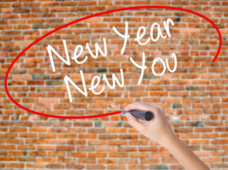 Woman Hand Writing New Year New You with black marker on visual screen. Isolated on city. Business concept. Stock Photo