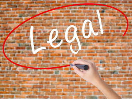 Woman Hand Writing Legal with black marker on visual screen. Isolated on bricks. Business concept. Stock Photo