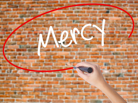 Woman Hand Writing Mercy with black marker on visual screen. Isolated on bricks. Business concept. Stock Photo