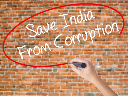 marchers: Woman Hand Writing Save India From Corruption with black marker on visual screen. Isolated on bricks. Business concept. Stock Photo