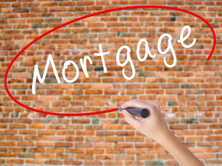Woman Hand Writing Mortgage with black marker on visual screen. Isolated on bricks. Business concept. Stock Photo Stock Photo