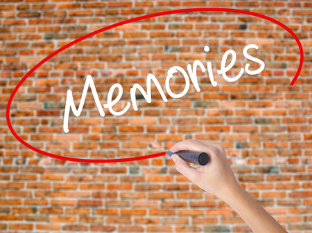 Woman Hand Writing Memories with black marker on visual screen. Isolated on bricks. Business, technology, internet concept. Stock Photo