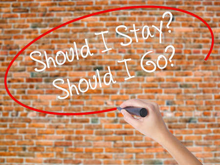 Woman Hand Writing Should I Stay? Should I Go? with black marker on visual screen. Isolated on bricks. Business concept. Stock Photo Stock Photo