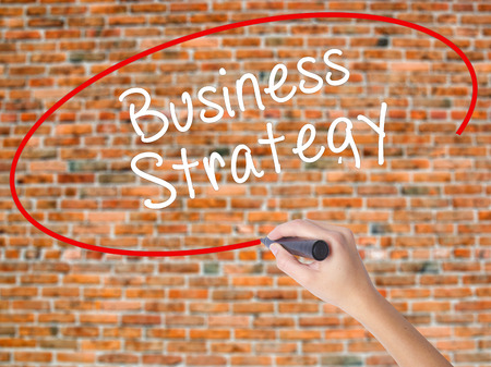 Woman Hand Writing Business Strategy with black marker on visual screen. Isolated on bricks. Business concept. Stock Photo