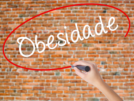 Woman Hand Writing Obesidade (Obesity in Portuguese)  with black marker on visual screen. Isolated on bricks. Business concept. Stock Photo