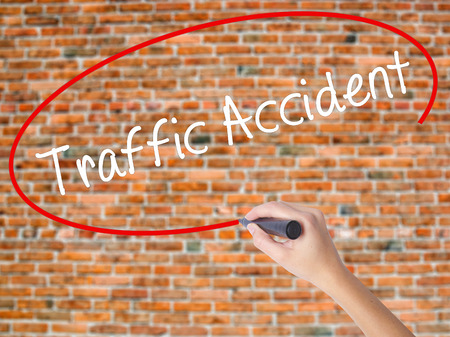Woman Hand Writing Traffic Accident with black marker on visual screen. Isolated on bricks. Business concept. Stock Photo