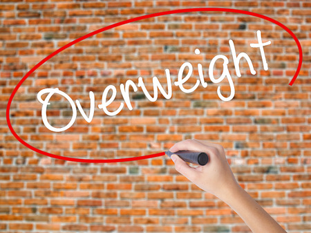 sedentario: Woman Hand Writing Overweight  with black marker on visual screen. Isolated on bricks. Business concept. Stock Photo