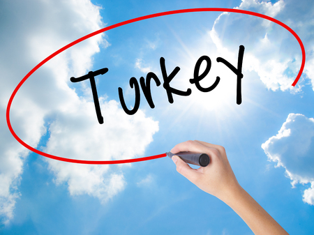 Woman Hand Writing Turkey  with black marker on visual screen. Isolated on Sunny Sky. Business concept. Stock Photo