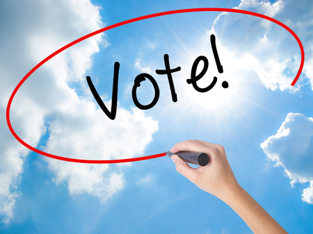 Woman Hand Writing Vote! with black marker on visual screen. Isolated on Sunny Sky. Business concept. Stock Photo