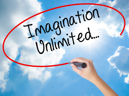 Woman Hand Writing Imagination Unlimited... with black marker on visual screen. Isolated on Sunny Sky. Business concept. Stock Photo
