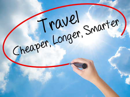 smarter: Woman Hand Writing Travel Cheaper Longer Smarter  with black marker on visual screen. Isolated on Sunny Sky. Business concept. Stock Photo Stock Photo