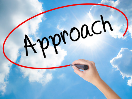 Woman Hand Writing Approach with black marker on visual screen. Isolated on Sunny Sky. Business concept. Stock Photo