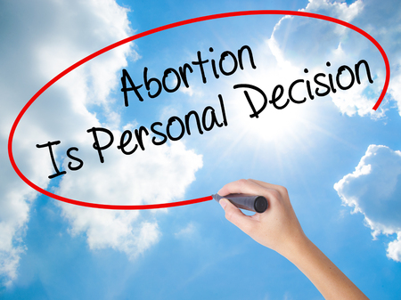 Woman Hand Writing Abortion Is Personal Decision with black marker on visual screen. Isolated on Sunny Sky. Business concept. Stock Photo