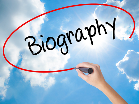 Woman Hand Writing Biography  with black marker on visual screen. Isolated on Sunny Sky. Business concept. Stock Photo