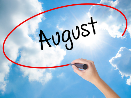 calendario julio: Woman Hand Writing August  with black marker on visual screen. Isolated on Sunny Sky. Business concept. Stock Photo Foto de archivo