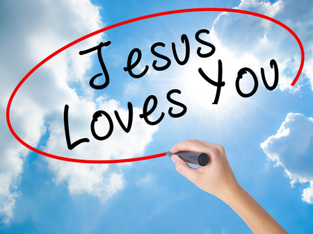 testament schreiben: Woman Hand Writing Jesus Loves You with black marker on visual screen. Isolated on Sunny Sky. Religion, technology, internet concept. Stock Image