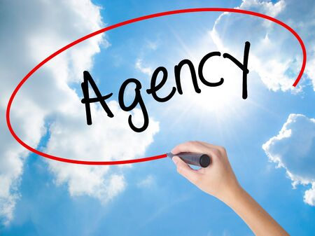 Woman Hand Writing Agency with black marker on visual screen. Isolated on Sunny Sky. Business concept. Stock Photo