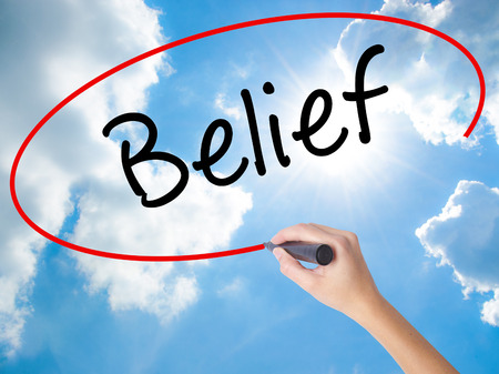 Woman Hand Writing Belief with black marker on visual screen. Isolated on Sunny Sky. Business concept. Stock Photo Stock Photo