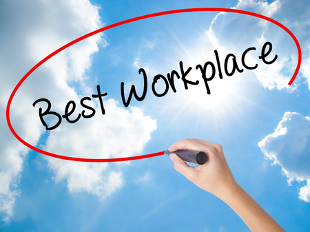 fulfilled: Woman Hand Writing Best Workplace with black marker on visual screen. Isolated on Sunny Sky. Business concept. Stock Photo