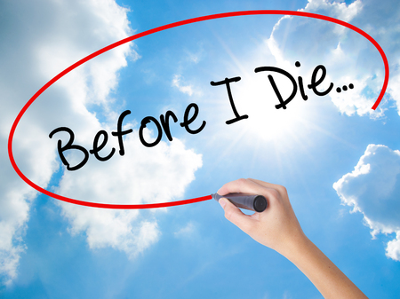 Woman Hand Writing Before I Die... with black marker on visual screen. Isolated on Sunny Sky. Business concept. Stock Photo Stock Photo