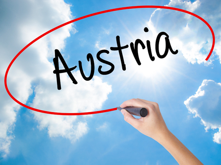 Woman Hand Writing  Austria with black marker on visual screen. Isolated on Sunny Sky. Business concept. Stock Photo