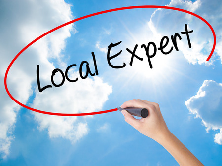 Woman Hand Writing  Local Expert with black marker on visual screen. Isolated on Sunny Sky. Business concept. Stock Photo