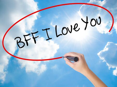 Woman Hand Writing BFF I Love You with black marker on visual screen. Isolated on Sunny Sky. Business, technology, internet concept.