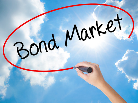 Woman Hand Writing Bond Market with black marker on visual screen. Isolated on Sunny Sky. Business concept. Stock Photo
