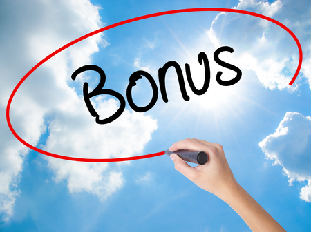 Woman Hand Writing Bonus with black marker on visual screen. Isolated on Sunny Sky. Business concept. Stock Photo Stock Photo