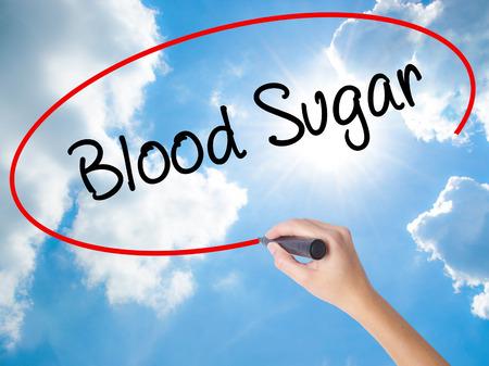 女性の手書く血糖ビジュアル画面に黒のマーカーで。晴れた空上に分離。ビジネス コンセプトです。ストック フォト