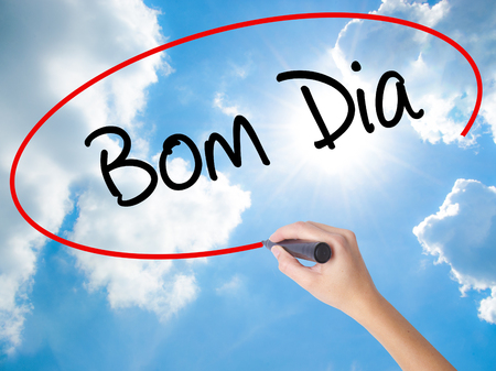 "Woman Hand Writing ""Bom Dia"" (In portuguese - Good Morning)  with black marker on visual screen. Isolated on Sunny Sky. Business concept. Stock Photo"
