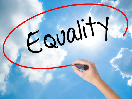 Woman Hand Writing Equality  with black marker on visual screen. Isolated on Sunny Sky. Business concept. Stock Photo