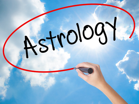 Woman Hand Writing Astrology with black marker on visual screen. Isolated on Sunny Sky. Business concept. Stock Photo