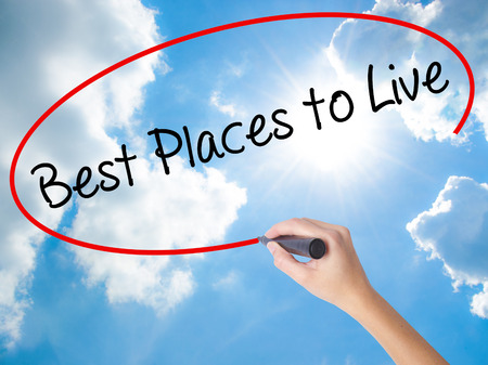 Woman Hand Writing Best Places to Live with black marker on visual screen. Isolated on Sunny Sky. Business concept. Stock Photo