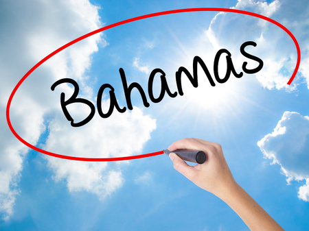Woman Hand Writing Bahamas with black marker on visual screen. Isolated on Sunny Sky. Business concept. Stock Photo