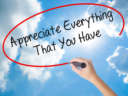 personal god: Woman Hand Writing Appreciate Everything That You Have with black marker on visual screen. Isolated on Sunny Sky. Business concept. Stock Photo Stock Photo