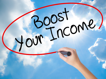 Woman Hand Writing Boost Your Income with black marker on visual screen. Isolated on Sunny Sky. Business concept. Stock Photo Stock Photo