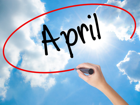 Woman Hand Writing  April  with black marker on visual screen. Isolated on Sunny Sky. Business concept. Stock Photo