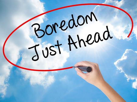 Woman Hand Writing Boredom Just Ahead with black marker on visual screen. Isolated on Sunny Sky. Business concept. Stock Photo