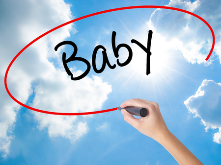 Woman Hand Writing Baby with black marker on visual screen. Isolated on Sunny Sky. Business, technology, internet concept.