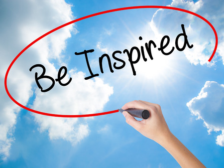 Woman Hand Writing Be Inspired with black marker on visual screen. Isolated on Sunny Sky. Business concept. Stock Photo