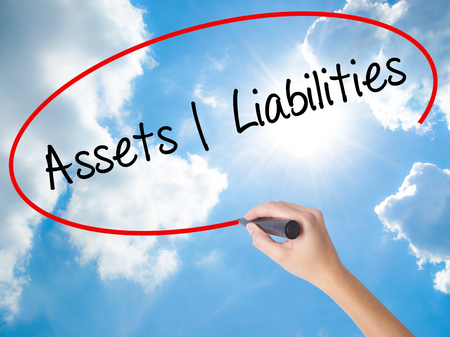 Woman Hand Writing Assets Liabilities with black marker on visual screen. Isolated on Sunny Sky. Business concept. Stock Photo